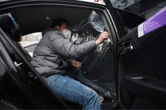 A worker installs a plastic sheet to separate the driver and passenger compartments in a car at a disinfection station for Chinese ride hailing company Didi, in Beijing. (Image: AFP Relaxnews)