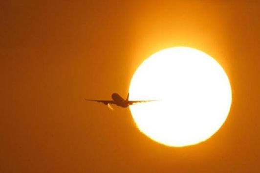 A passenger aircraft is silhouetted against the rising sun during the early morning. (Image: Reuters)