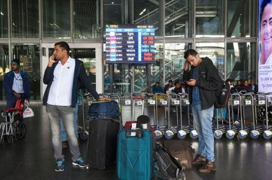 Flight passengers wait for transport vehicles outside the NSCBI Airport as taxies were off the roads due to the nationwide strike called by trade unions, in Kolkata. (Image: PTI)