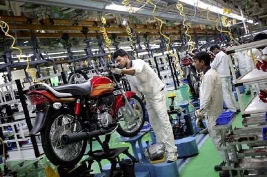 Employees work on an assembly line of Hero Motocorp during a media tour to the newly opened plant in Neemrana