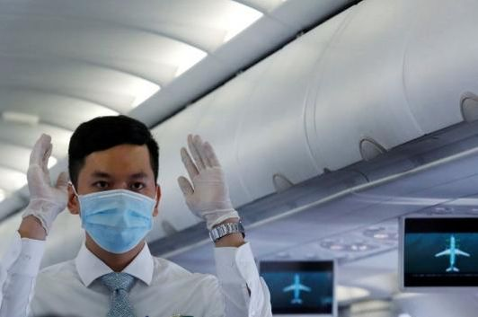 An attendant wearing a protective mask guides the flight safety procedures before take off of a Vietnam Airlines flight, following an outbreak of the novel coronavirus, at Danang airport in Danang city, Vietnam February 23, 2020. REUTERS/Kham/Files