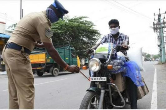 Tamil Nadu Police paints the number plate of a two-wheeler.